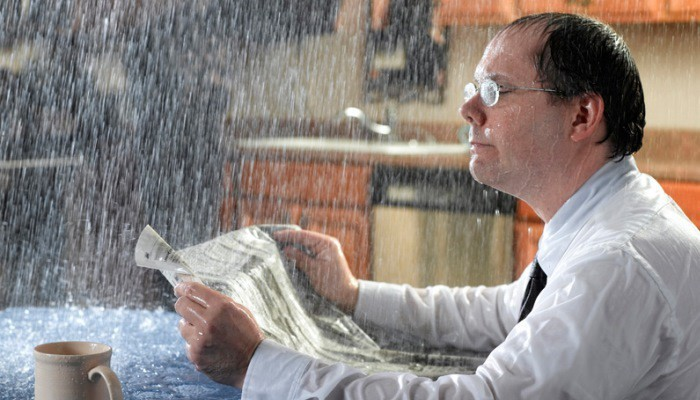 businessman reading newspaper while raining