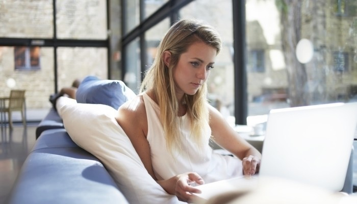 beautiful young freelancer using laptop on couch