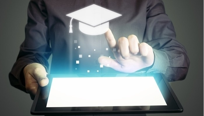 graduate holding tablet computer