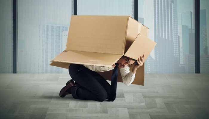 Businessman hiding in box