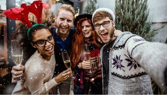 group of smiling men and women taking selfie outdoors while snowing
