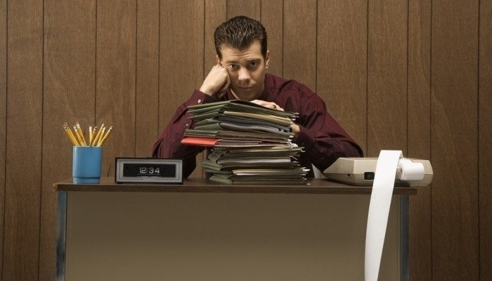 businessman with bored expression sitting at desk piled high with folders
