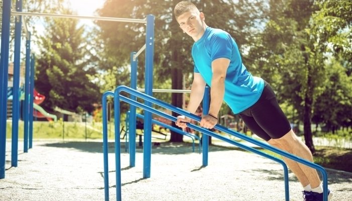 man exercising in outdoor park gym