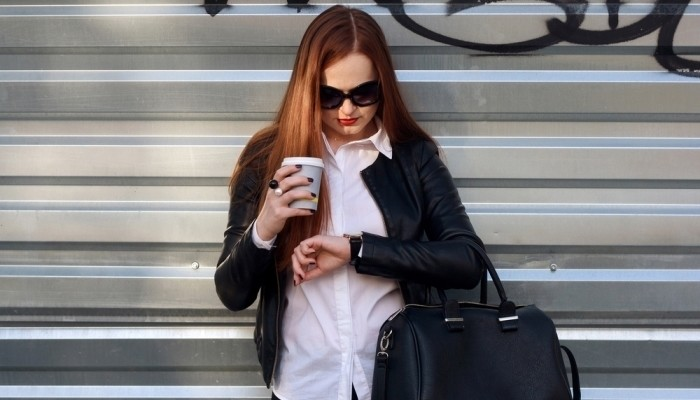 woman drink coffee and looking watch outdoor