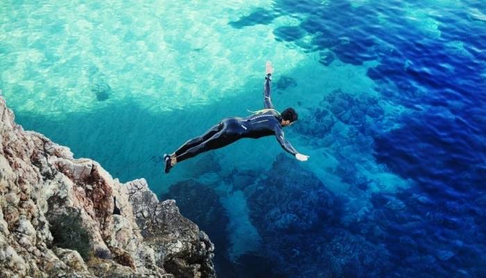 man diving from a cliff