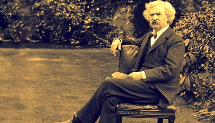 mark twain sitting on a chair