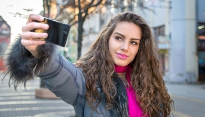 Smiling woman taking a selfie photo in an urban street in winter