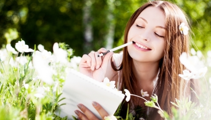 beautiful young brunette woman writing in her diary on the meadow with white flowers