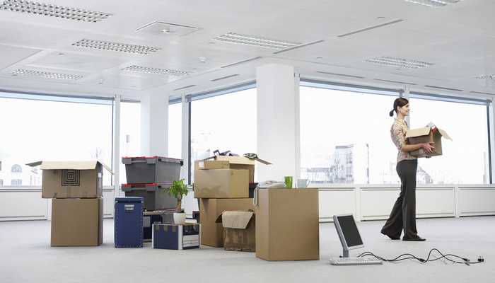 Woman carrying box in new office