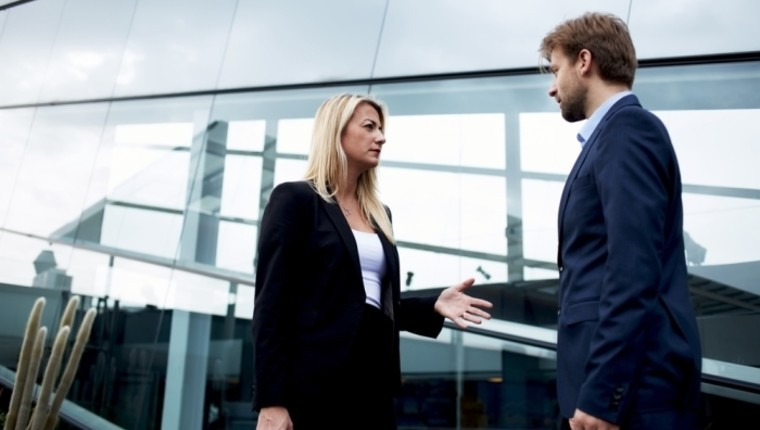 attractive businesswoman talking to man