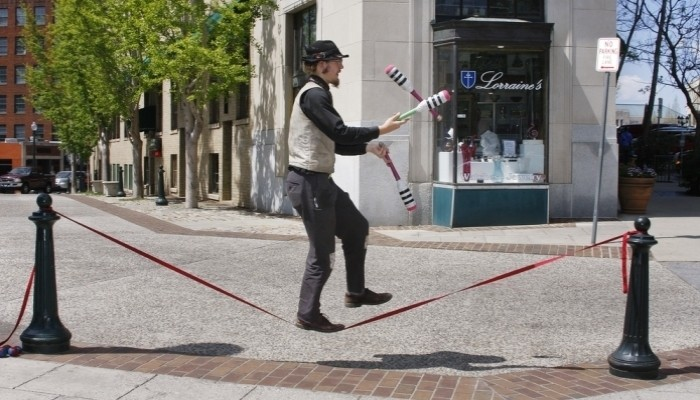 man juggling and walkign on tightrope