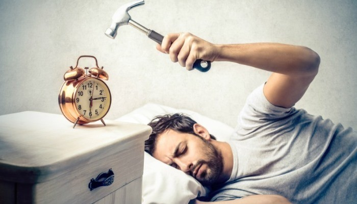 Man hitting alarm clock with hammer