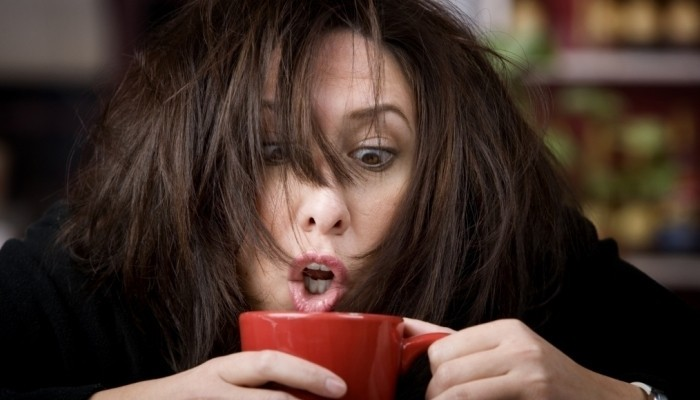 Woman waking up and drinking coffee
