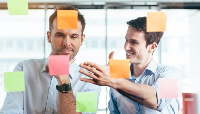 Businessman discussing plans with sticky notes