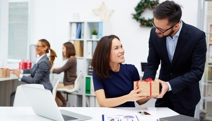 businessman giving his colleague christmas present
