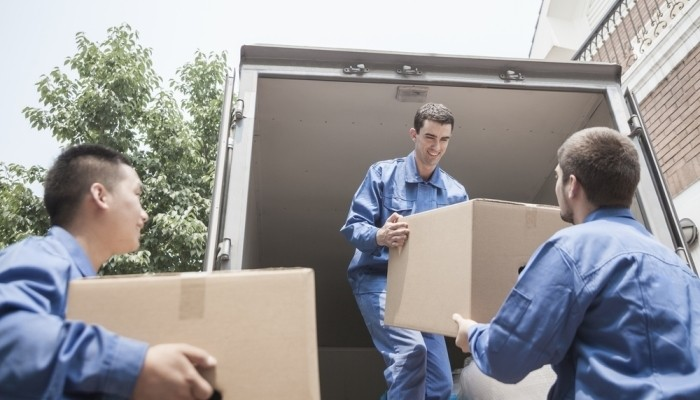 Movers unloading boxes from a truck
