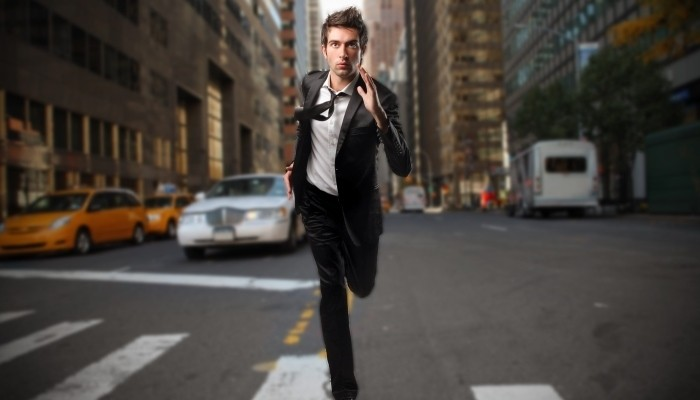 Businessman running down street