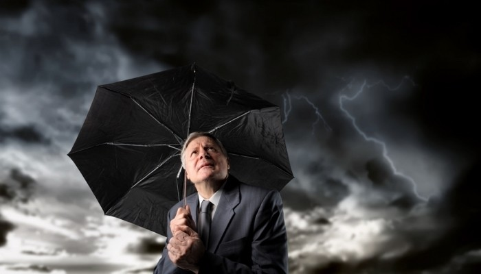 Businessman holding umbrella in storm