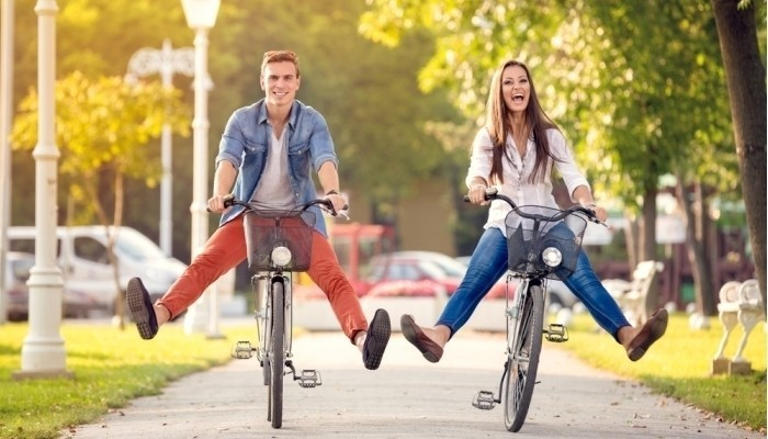 happy funny young couple riding on bicycle